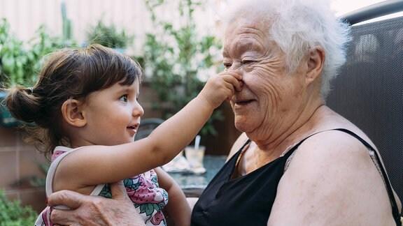Ein kleines Mädchen sitzt auf dem Schoß einer älteren Dame und fasst ihr an die Nase.
