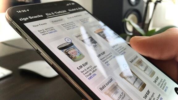 Nahaufnahme eines Smartphones mit der App eines Lebensmittellieferdienstes und verschiedener Eiscremebecher zur Auswahl. Wird von Hand gehalten, unscharfer Hintergrund.