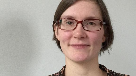 Junge Frau mit Brille lächelt