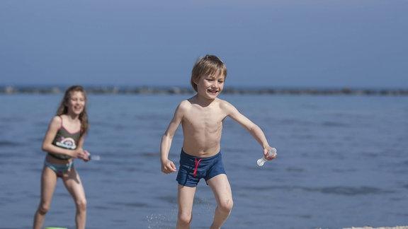 Mädchen und Junge spielen an einem Strand