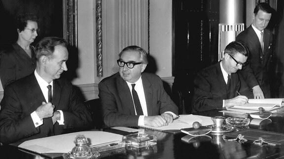 An einem glänzenden Tisch sitzen drei Männer. Einer schreibt.