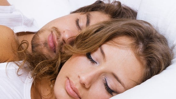 Ein Liebespärchen liegt im Bett und schläft