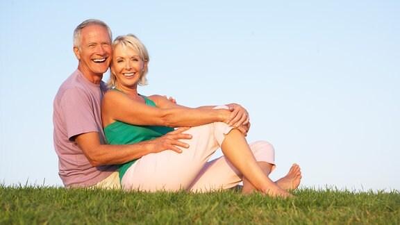 ein älteres Pärchen sitzt auf einer Wiese und lacht in die Kamera