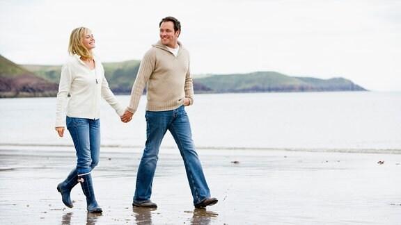 Mann und Frau laufen Hände haltend am Strand