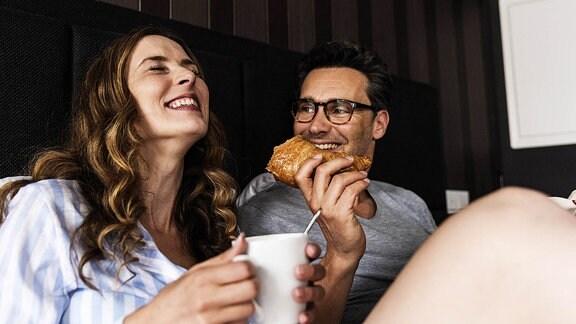 Lachendes Paar mit Frühstück im Bett.