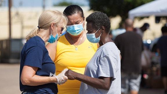 Drei Frauen mit Mundschutz stehen beieinander, eine Frau hält die Hand einer anderen Frau.