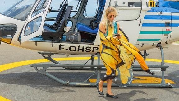 Junge weiße Frau vor Hubschrauber