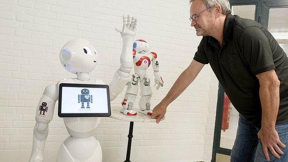 Ein humanoider Roboter Pepper (li.) reicht einem Mann die Hand
