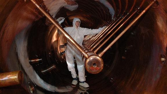 Ein Mann in einem weißen Schutzoverall steht im Teilchenbeschleuniger UNILAC im GSI Helmholtzzentrum für Schwerionenforschung - einer kupferfarbenen Röhre mit verschiedenen Streben.