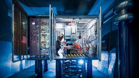 Eine Forscherin steht am Startpunkt der Beschleunigeranlage - einer großen Box mit zahlreichen Kabeln und Schaltern.