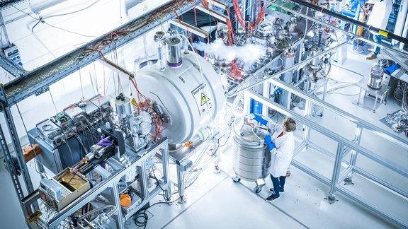 Eine Person steht in weißem Kittel an einer großen technischen Anlage mit vielen Kabeln - der Ionenfalle SHIPTRAP.