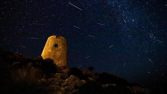 Perseiden-Meteoritenschauer und Milchstraße und mittelalterlicher Turm im Vordergrund