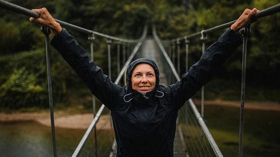 junge Frau zentral im Bild auf einer Hängebrücke mit Regenjacke und aufgezogener Kapuze bei Regenwetter, hält sich links und rechts an Geländer fest und blickt nach oben