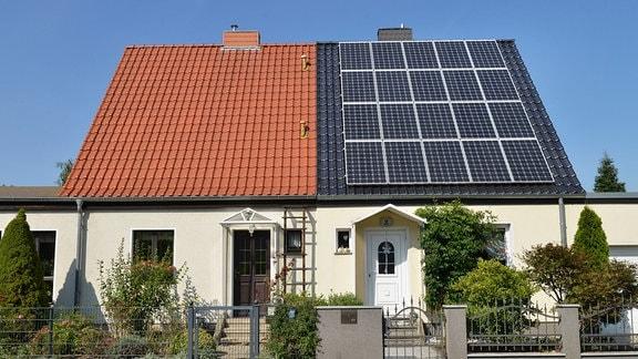 Doppelhaus - das linke Hausdach mit klassischen Schindeln, das rechte ist mit Solarmodulen bestückt.