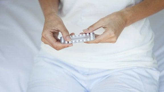 Frau hält Blister mit Pillen