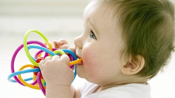 Baby mit Plastik Spielzeug