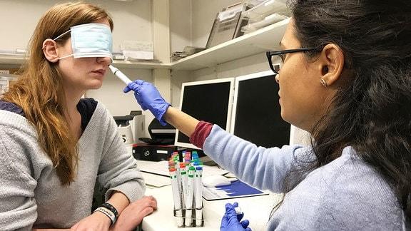 Podcastreporterin Daniel Schmidt hat die Augen verbunden während ihr eine Forscherin eine Geruchsprobe unter die Nase hält.