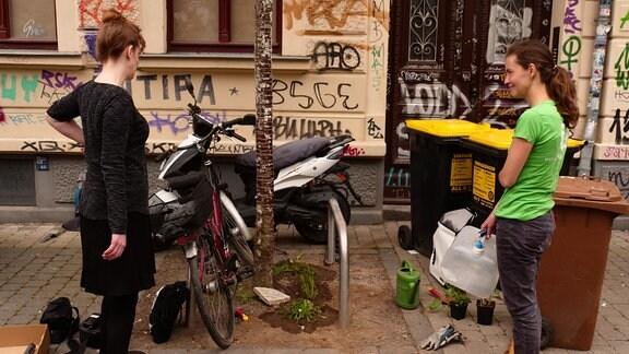 Zwei Frauen stehen vor einem frisch eingepflanzten Baumbeet in einem urbanen Kontext mit Fahrrädern und Mülleimern drum herum.