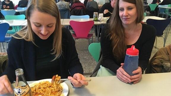 Zwei junge Frauen sitzen gemeinsam in der Kantine. Die Frau links hat ein Nudelgericht vor sich, die Frau rechts eine Flasche mit Flüssignahrung