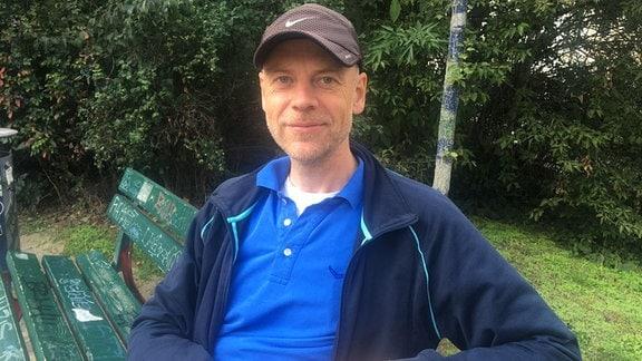 Ein Mann mit Kappi sitzt auf einer Parkbank