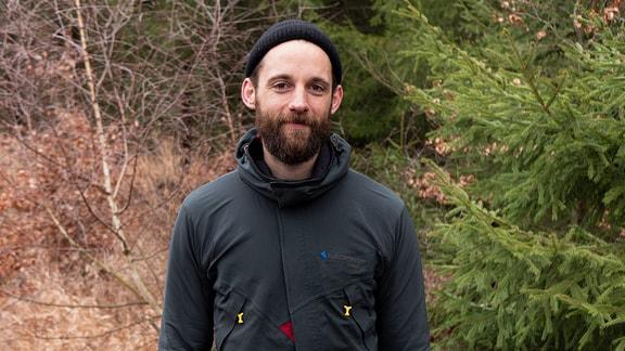 Ein junger Mann mit vollem Bart und einer Mütze auf dem Kopf steht vor einem Waldstück und schaut in die Kamera