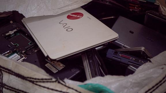 Zahlreiche Laptops liegen bei einem Schrotthändler in einem großen Plastiksack