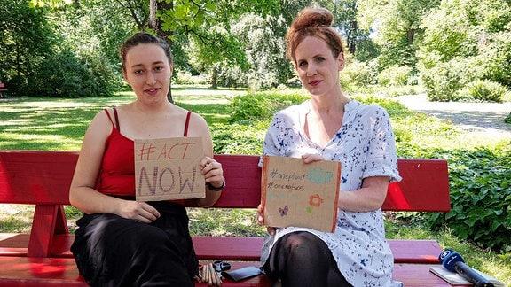 Zwei Frauen sitzen auf einer Parkbank.