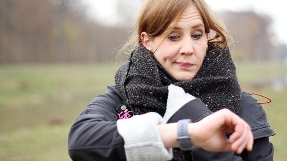 Eine Frau schaut auf ihre Armbanduhr.