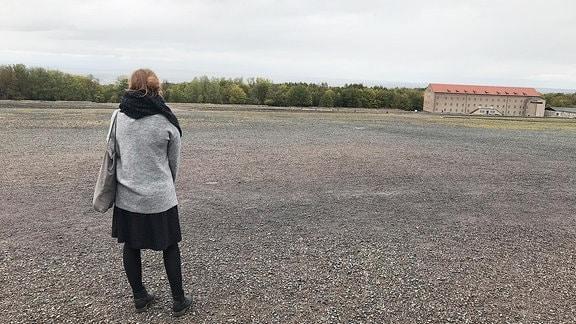 Eine Frau steht auf einer Anhöhe.