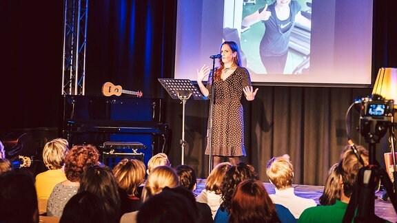 Eine Frau steht auf einer Bühne vor Publikum.