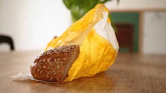 Auf dem Bild ist ein halbes Brot zu sehen, dass in einer gelb bedruckten Papiertüte vom Bäcker liegt.