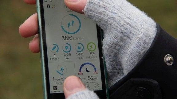 Ein handydisplay, auf dem verschiedene Fitnesswerte wie Schrittzahl und Puls angezeigt werden.