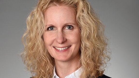 Eine Frau im Anzug und lockigen, blonden Haaren schaut lächelnd in die Kamera