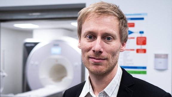 Der Mediziner Stefan Ehrlich steht vor einem Magnet-Resonanztomografen an der Uni Dresden