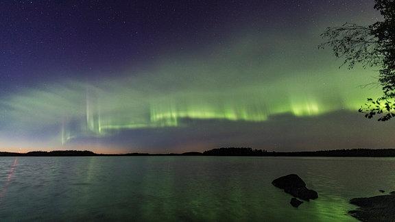 Die Polarlichtdünen erscheinen als grün gefärbtes und gleichmäßiges Wellenmuster, das an einen gestreiften Wolkenschleier oder Dünen an einem Sandstrand erinnert