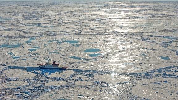 Luftaufnahme eines Forschungsschiffs im Meer mit vielen kleineren und größeren Eisschollen drumherum, eng aneinanderliegend.