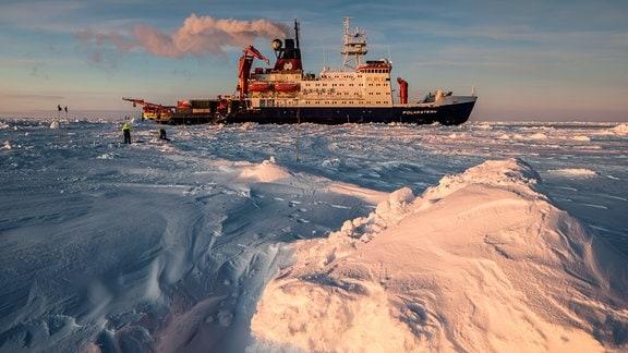 Ein Forschungsschiff im Eis mit Abendsonne.