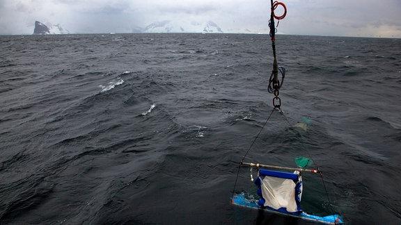Ein viereckiges Netz taucht ins Wasser ein.