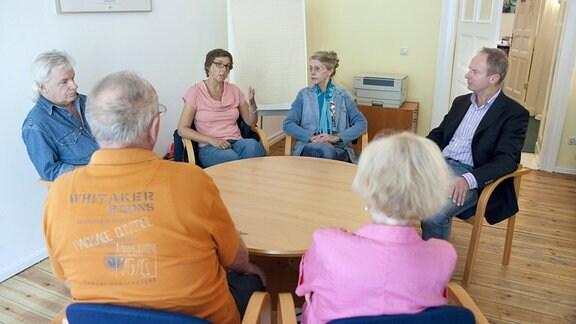 Erwachsene sitzen an einem runden tisch.