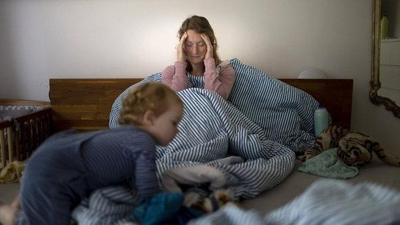 Eine Mutter hält sich den Kopf, während ein Kleinkind über ihr Bett krabbelt.