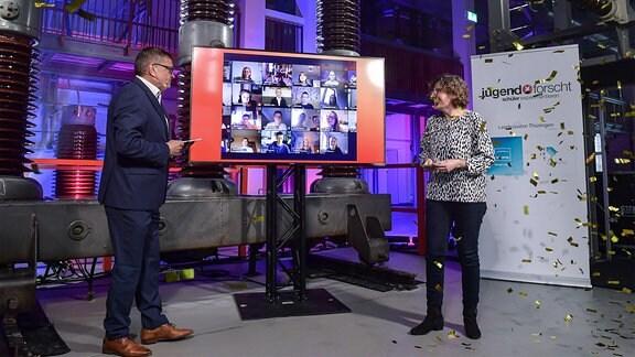 Ein mann und eine Frau moderieren eine Veranstaltung – in der Mitte ein Bildschirm mit vielen Webcambildern aus Videoschalten