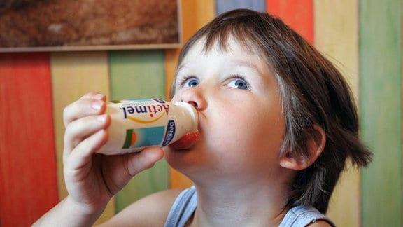 Kind trinkt einen probiotischen Trinkjoghurt aus einer kleinen Plastikflasche, blickt dabei nach oben.