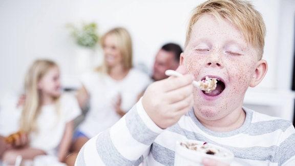 Ein rothaariger, hellhäutiger Junge isst mit geschlossenen Augen genüsslich einen Joghurt mit Müsli, im Hintergrund sind unscharf Mutter, Vater und Schwester zu erkennen.