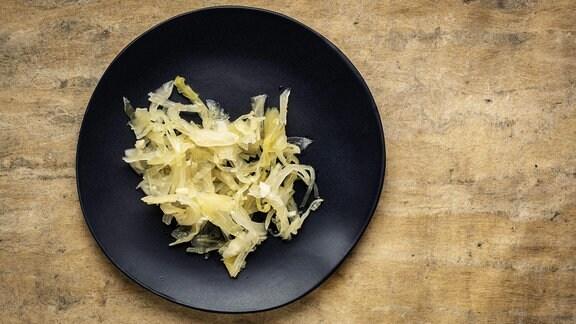 Blick von oben auf deinen schwarzen Teller auf einem Holztisch. Dort ist ein wenig Sauerkraut angerichtet (helles, weich-feuchtes Kraut)