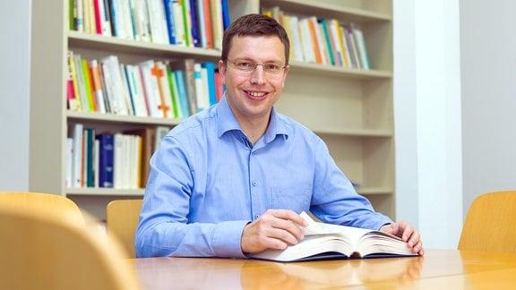 Ein lächelnder Mann sitzt allein an einem Tisch, im Hintergrund ein Bücherregal