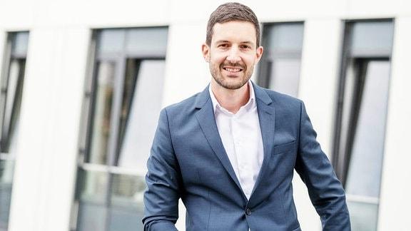 Professor Hendrik Hildebrandt posiert für ein Foto im Anzug und lächelt in die Kamera.