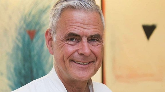 Porträt von Prof. Uwe Janssens: Mann mit kurzen, grauen Haaren, ohne Bart und Brille, mit weißem Kittel. Hintergrund gelblich, unscharf mit Muster und Dreiecken.