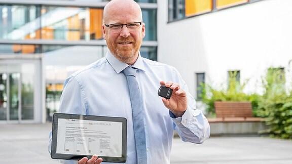 Ein Mann hält ein Tablet und einen Tracer - Dr. Stefan Moritz von der Universitätsmedizin Halle/S.