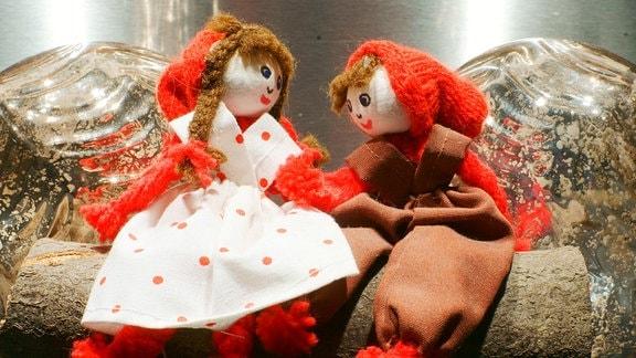 Zwei Puppen mit Weihnachtsmützen