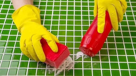 Hände in Gummihandschuhen verteilen Scheuermittel auf Fliesen.